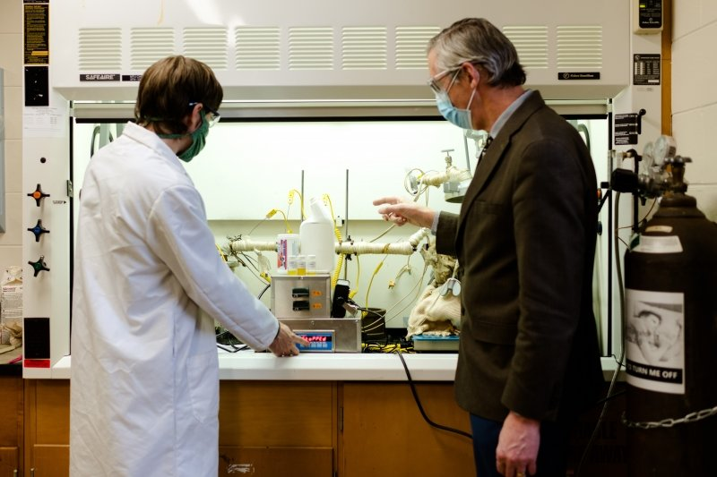 two people stand in front of a chemistry hood