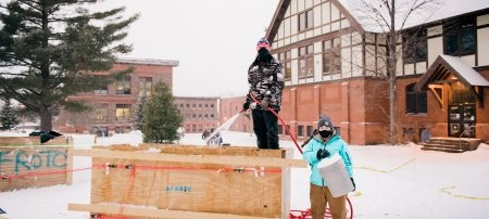 Two students wearing masks work on snow statue
