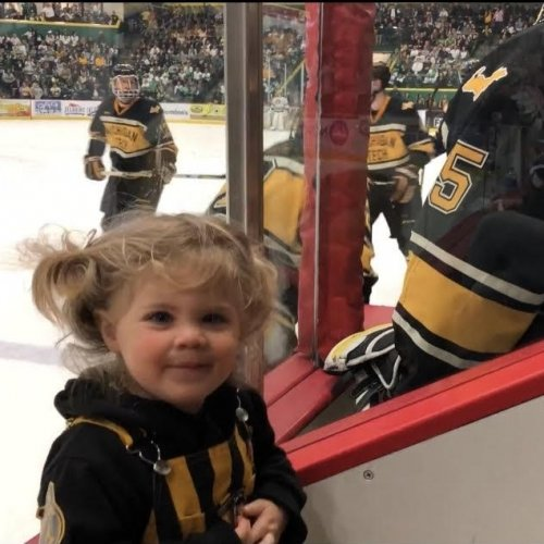 A little girl in pigtails smiles next to the Michigan Tech hockey bench with players on it with other players on the ice in the background