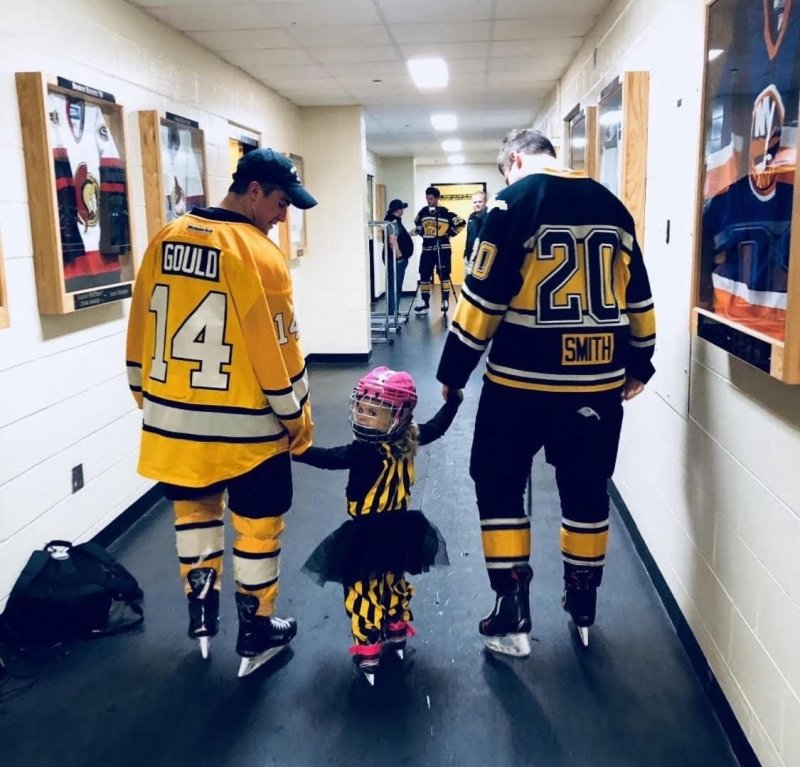 A little girl in a tutu holds the hands of two hockey players in the hall with their backs to us in Michigan Tech's John MacInnes student ice arena.