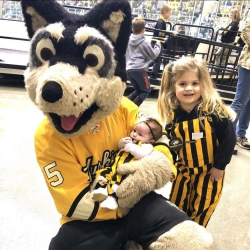 A giant Husky in a Michigan Tech jersey holds a tiny baby in striped overalls while a little gear also in striped overalls stands nearby at a Michigan Tech Hockey game in an ice arena