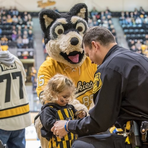 A little girl holds the handcuffs of a kneeling police officer with a giant Husky mascot looking on in an ice rink at a hockey gsme in the stands.