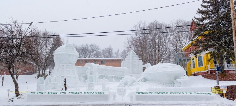 View of huge snow statue next to fraternity house