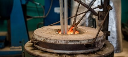 A hot forge holds bars of raw aluminum.