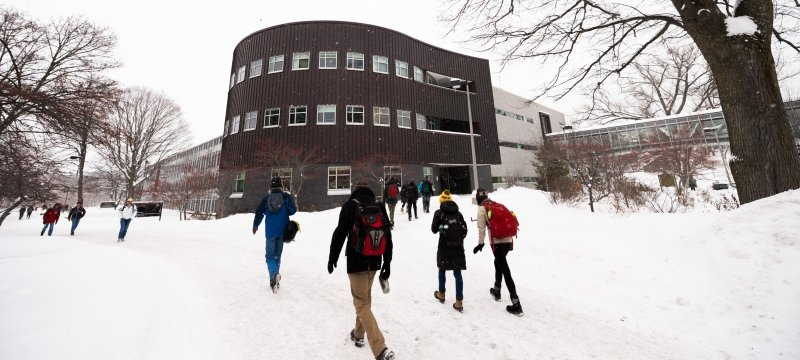 Campus view of Rekhi Hall and walkways in winter.