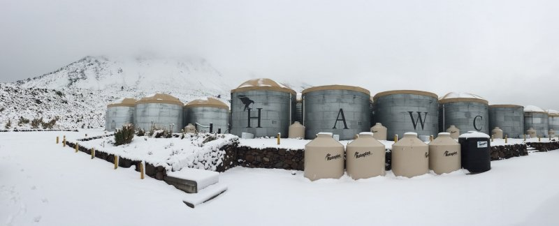 The cylindrical light detectors at HAWC, with snow covering the ground and the hillside in the background.