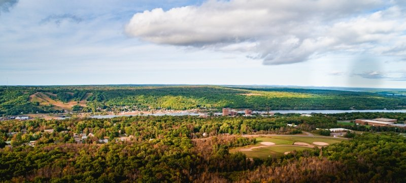 Drone image of Michigan Tech's campus, Keweenaw Waterway, and surrounding woods.