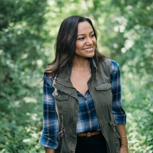 A woman smiles at something in the distance in a green forest.