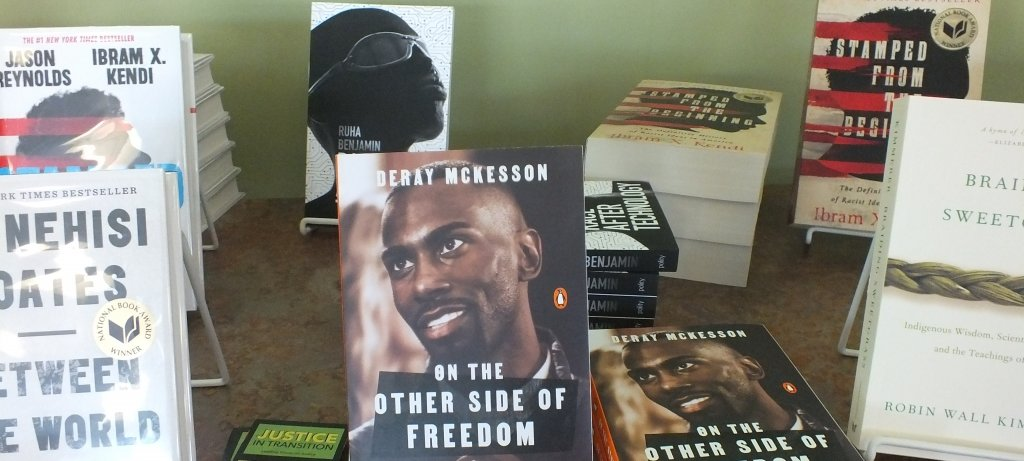 books in stands and stacked on a library table with a green wall in background: from left, counterclockwise, Ta-Nahesi Coates, Between the World and Me; On the Other Side of Freedom, DeRay McKesson; Braiding Sweetgrass, Robin Wall Kimmerer; Stamped from the Beginning, Ibrim X. Kendi, Ruha Benjamin book cover with black woman's head and glasses.