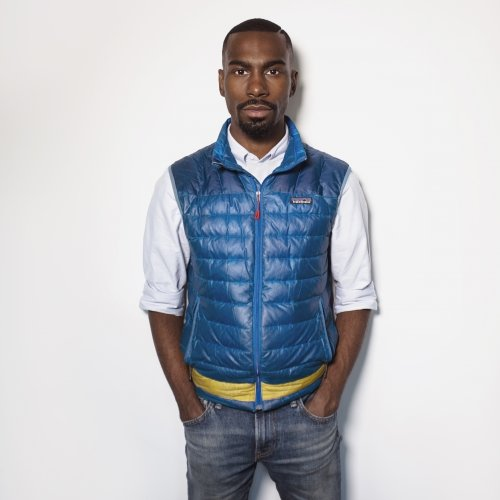 A man stands in a puffy vest with his hands in his pockets looking at the camera in front of a white background.