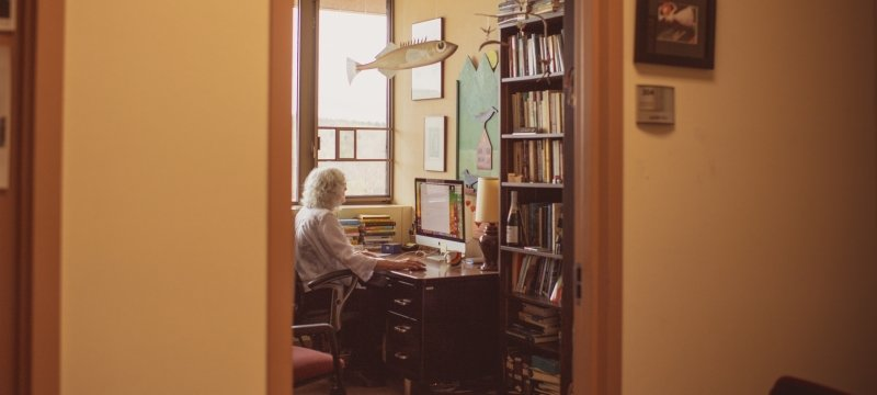 A woman sits at a desk inside an office working at her computer as the camera looks in outside from the hallway. There is a hanging wooden fish sculpture, books, and a window in the background at a University.