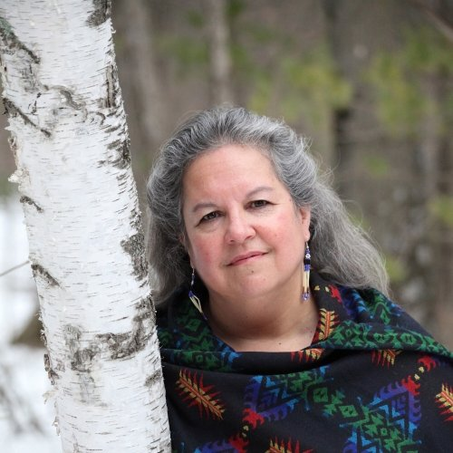 A woman leans against a white birch tree in the forest, hair blowing in the wind as she smiles at the camera.