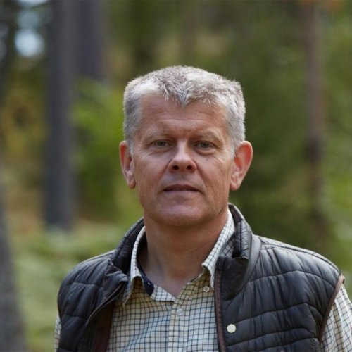 A man in a puffy vest with gray hair looks at the camera with a forest in the background.