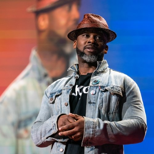 a man in a fedora wearing a headset on a stage at a TED talk with his image projected on a screen behind him.