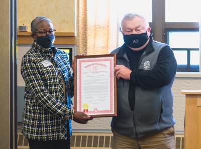 Two people hold a framed document between them.