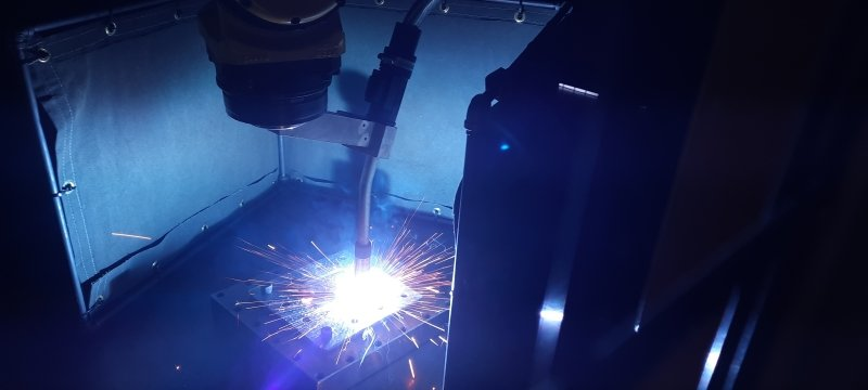 A MIG robot prints a metal part as sparks fly from the tip of the welder on a black background.