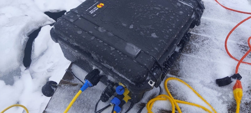 Test equipment in a black box on a snow-covered dock next to the ice in winter with yellow cords and red and black plugs