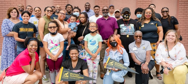 A group of Michigan Technological University Black alumni and prospective students pose for a group shot in front of a brick wall in Detroit's Greektown.