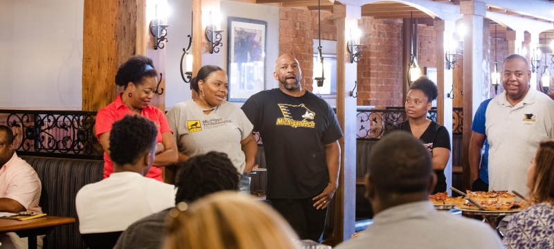 Five people stand in a restaurant near a pizza table with others sitting in the background with wood-finished walls and many wearing Michigan Technological University Huskies t-shirts and other swag at the African American Alumni Association annual picnic in Detroit.