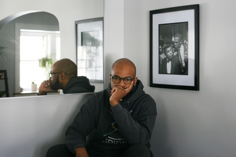 A young man with chin cupped in hand reflects in front of a portrait of Mohammed Ali and Malcom X.