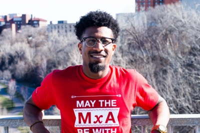 A man with his arms draped on a concrete wall in New York City wearing a red shirt that says MxA = Force tech humor for May the Force Be With You.