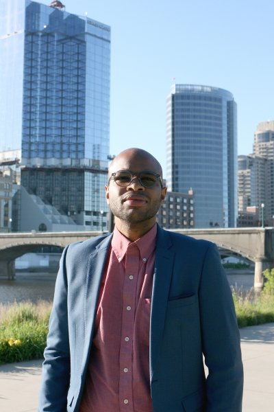 A young man stands in front of a bridge and cityscape under a blue sky in Grand Rapids, Michigan. He is wearing a suit.