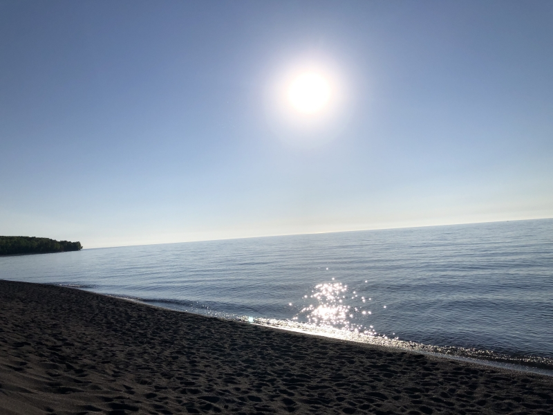 The sun shines over a rocky beach with the tree-lined shoreline in the distance.