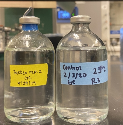 Two clear bottles with water in them that are labeled with the dates certain bacteria in the water in the bottles were collected.