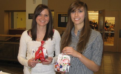 Heather Marker (left) and Alex Mallos (Right) are thrilled with their holiday gift bags from the University Women's Connection.
