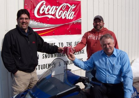 Gary and Rob Scholie (standing, left to right), owners of Coca-Cola of Hancock, celebrate the Coca-Cola Foundation's $10,000 donation to the SAE Clean Snowmobile Challenge with Challenge organizer Jay Meldrum.