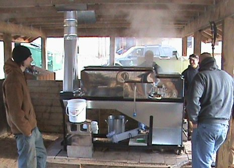 Michigan Tech Forestry and Environmental Resource Management (FERM) members tend the maple syrup evaporator, keeping the fire going, watching tap levels in the pans, making sure it does not  boil over and drawing off the syrup.
