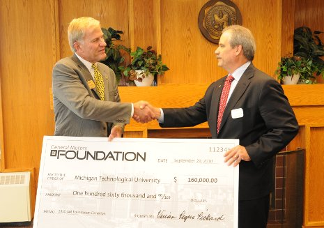 Terry Woychowski, at right, a Tech alumnus and vice president of General Motors, presents President Glenn Mroz with a contribution from the GM Foundation.