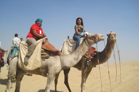 Jasmin Francisco, at right, and Semester at Sea friend Marie Delacruz ride camels through  the Sahara Desert.