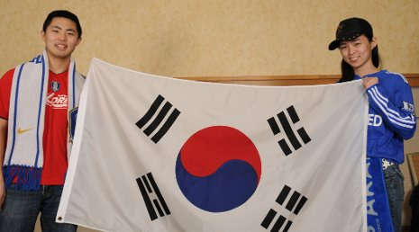 Michael Godfrey and Samantha Leonard hold the taegukgi, the flag of South Korea.