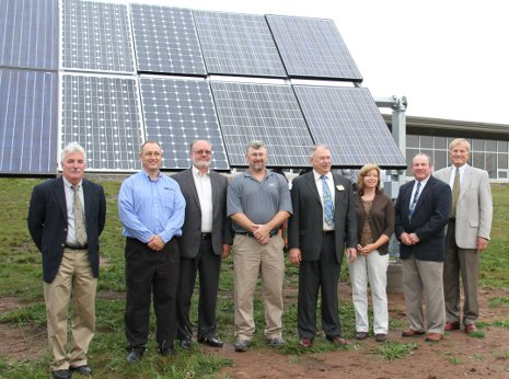 University and corporate officials stand by the Michigan Tech Solar Photovoltaic Research Facility during dedication ceremonies.