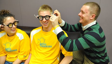 Cody Kangas, assistant director of pre-college outreach at Michigan Tech, fits Dow Corning self-adjusting eyeglasses on Mind Trekkers student volunteers, who will demonstrate the glasses and other science