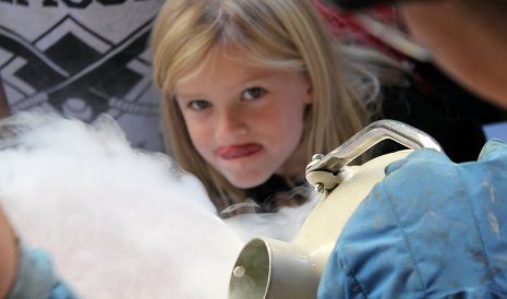 A little girl can't wait to taste liquid nitrogen ice cream.