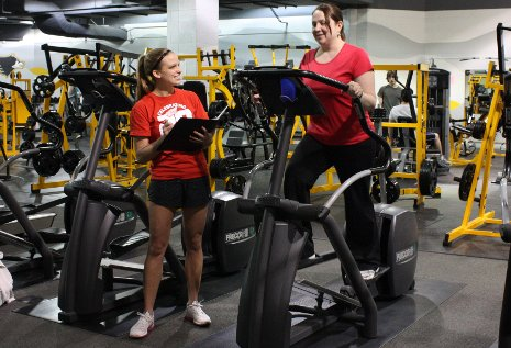 Crystal Verran works out on an elliptical machine under the watchful eye of personal trainer and kinesiology student Rosanna Chopp.