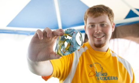 A Michigan Tech Mind Trekkers student volunteer holds a soda can ripped apart by a pingpong ball.