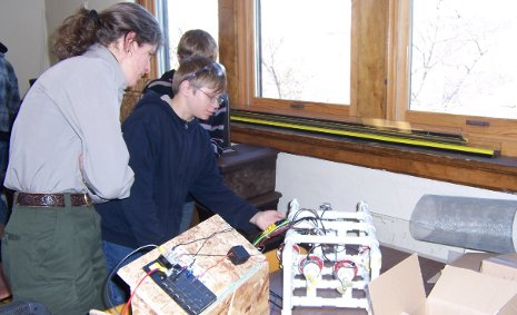 Dollar Bay High School Enterprise student shows an Isle Royale National Park ranger how their remotely operated vehicles work to locate invasive zebra mussels.