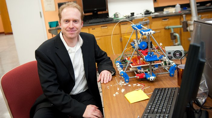 Joshua Pearce, organizer of the 3D Printers for Peace Contest, with one of the 3D printers used for research and teaching in his lab.