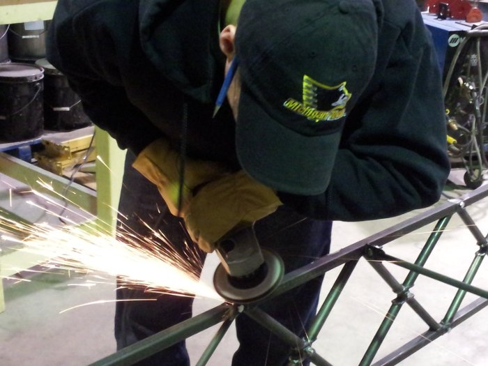 Steel Bridge team member Woody Beardsley grinds the top rails of Michigan Tech's Steel Bridge entry to make them smooth.