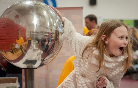A startling experience: Touching a Van de Graaff generator makes a girl's hair stand on end.