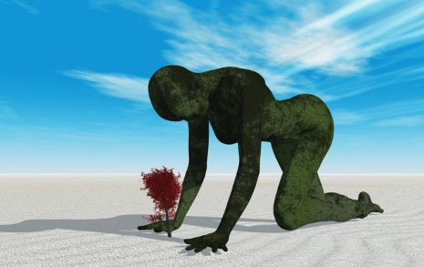 Graphic of a large green person crawling in the sand over a tree.