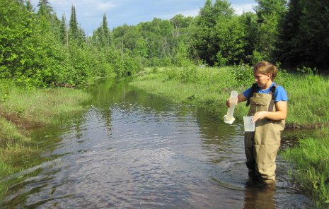 Undergraduate Faith Lambert sampling Hills Creek water upstream of the main restoration site.