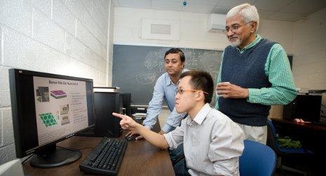 Sanjeev Gupta and Jarvis Loh work with Physics Chair Ravindra Pandey on his graphene research.