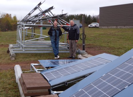 Solar energy scientist Joshua Pearce, left, and Jay Meldrum, director of the Keweenaw Research Center, with the array of solar panels behind KRC. Even on this gloomy day, the solar cells were cranking out electricity.