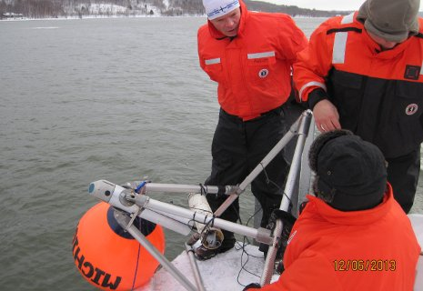 GLRC staff Michael Abbott, Jamey Anderson and Colin Tyrrell prepare to deploy the under-ice observatory from the research center's long dock. The orange float kept the device upright as it sank to the bottom.