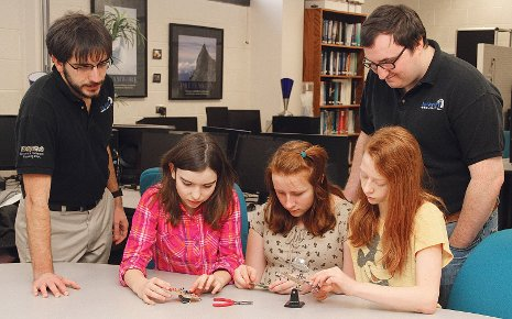 Blue Marble Security Enterprise students help middle schoolers assemble a heart monitor from a kit designed and built by the Enterprise. From the left, Philip Wolschendorf, Olivia Hohnholt, Hannah Hansen, Geneva Archer and Mike Switala.