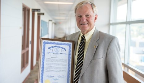 Glenn Mroz accepted a plaque from the State of Michigan, honoring Michigan Tech.